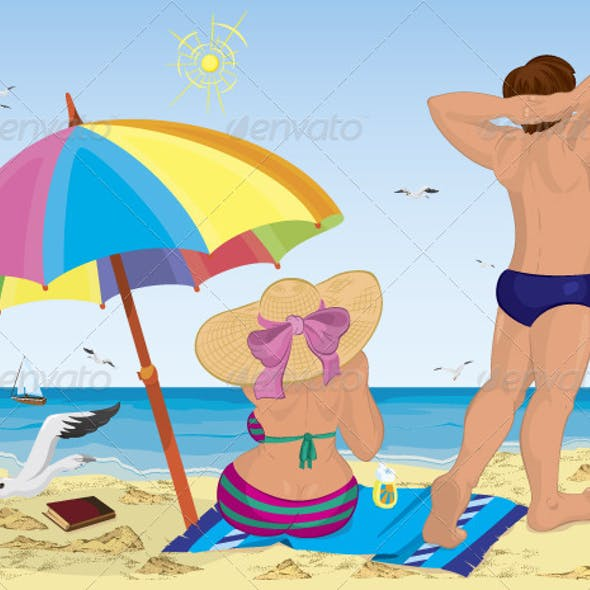 Married couple on the beach under umbrella