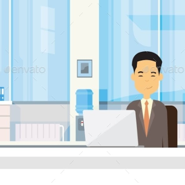 Asian Business Man Sitting at Desk in Office