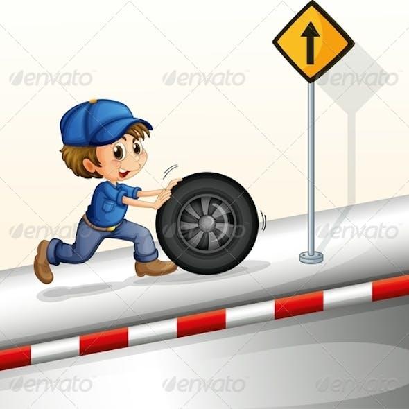Smiling mechanic pushing a tire