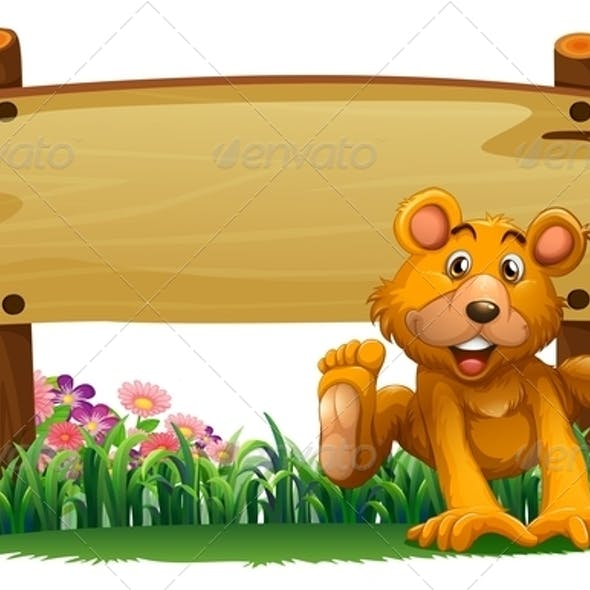 Playful bear with empty wooden signboard