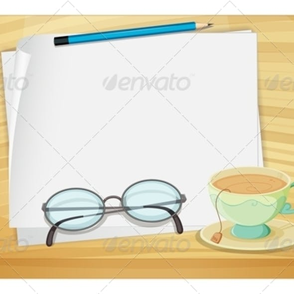 Wooden Table with an Empty Paper and Tea Cup