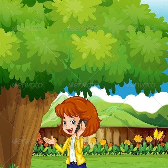 Woman with a Cellphone Standing Under a Tree
