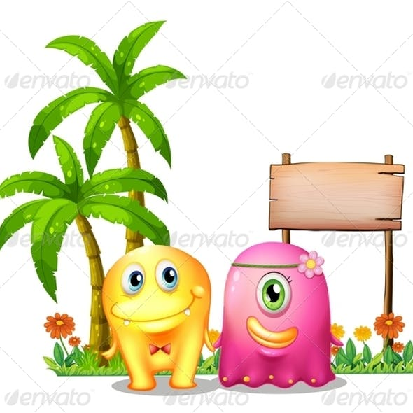 Yellow and Pink Monster Couple Standing by a Sign