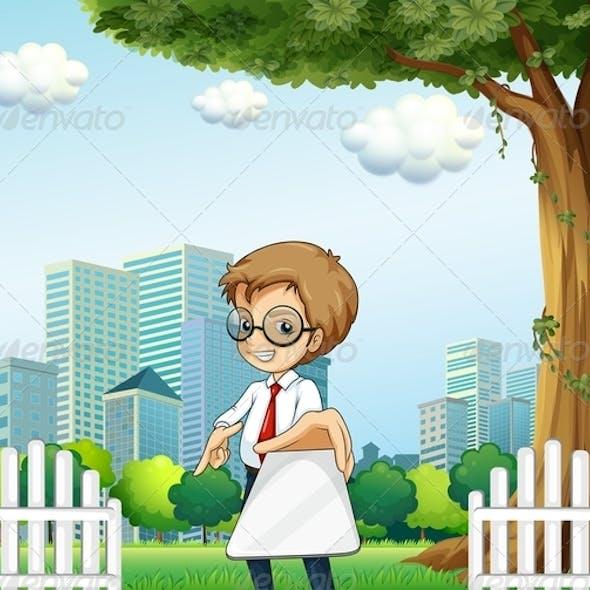 Businessman Holding a Gadget Under a Tree